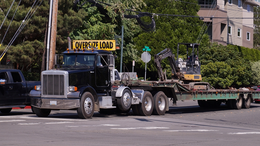 A truck with a wide semi-trailer for hauling oversized loads.